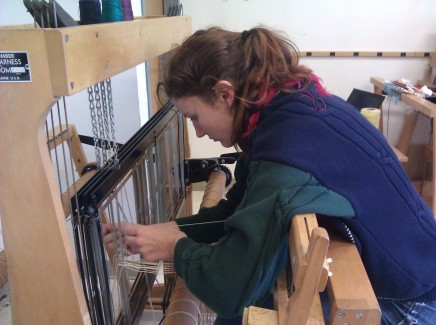 Stringing the heddles of the loom.
